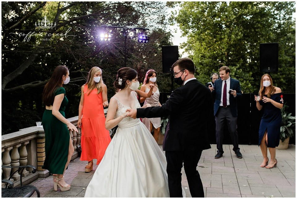 Bride and groom and guests dancing at reception