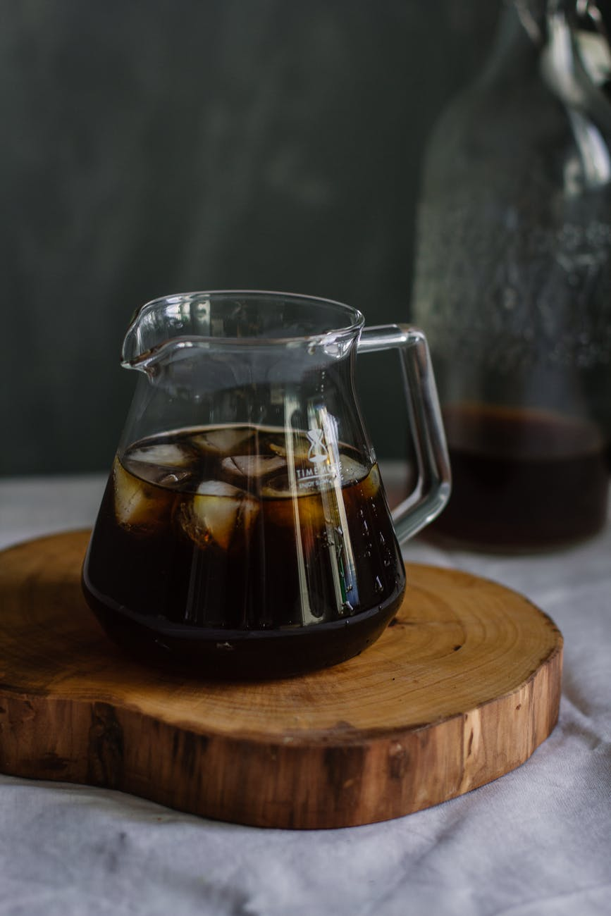 clear glass pitcher with cola and ice on wooden chopping board