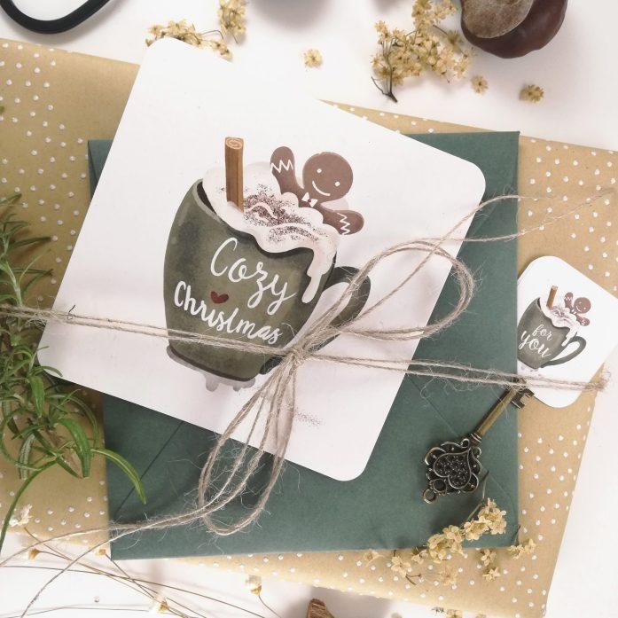 Cozy Christmas - Weihnachtskarte mit Umschlag auf einem verpackten Geschenk