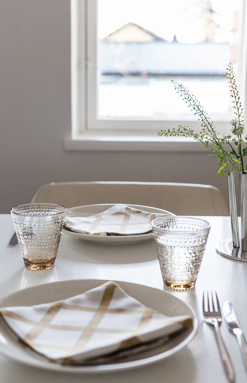 Kodikas kattaus, Iittala Kastehelmi lasit, Marimekko Quilt lautasliinat, Olki