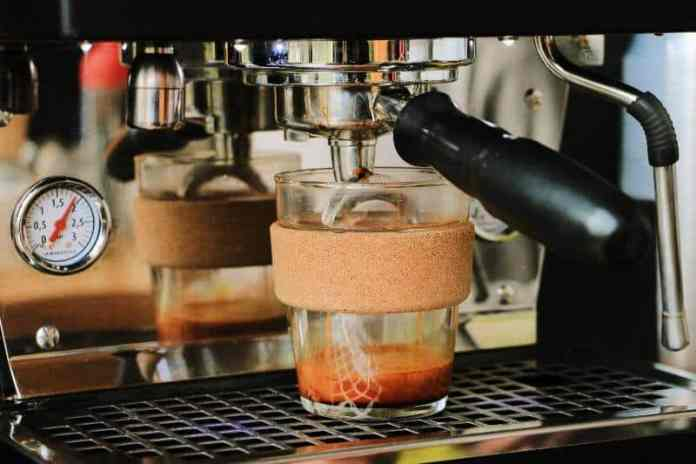 super automatic coffee maker with coffee cup underneath the spout