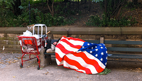 a man sleeping on a park bench with an American flag item being used as a blanket