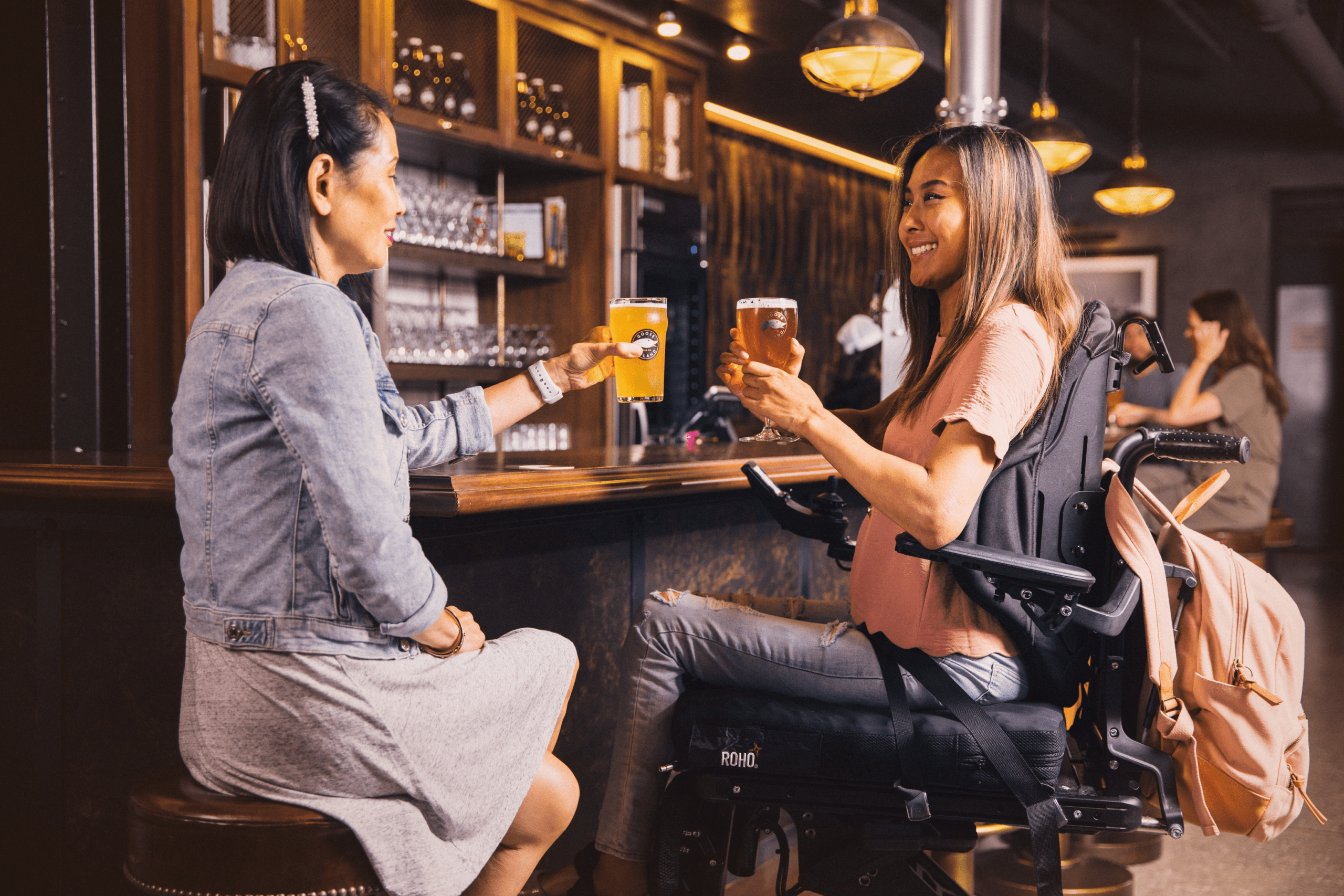 A woman in a wheelchair and her friend at a bar
