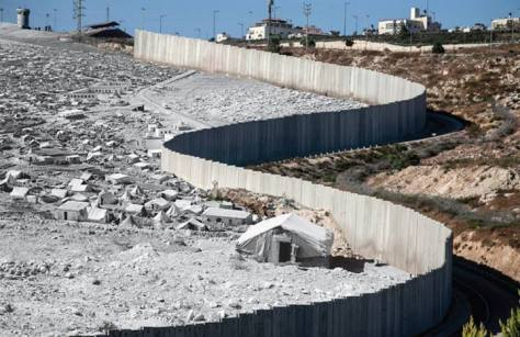 Black-and-white photo: Dheisheh refugee camp after the 1948 partition. From the UNRWA photo archive. Color photo: A segment of the Israeli separation wall near Beit Hanina in Jerusalem, 2012. By Tanya Habjouqa.