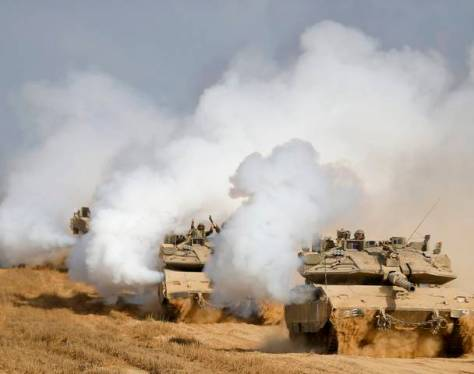 Israeli soldiers from the armoured corps gestures atop tanks after returning to Israel from Gaza August 5, 2014. Photo by Reuters