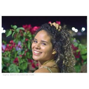 Foto de uma garota em primeiro plano e uma roseira ao fundo.