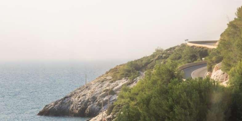 Encosta rochosa e mar vistos do trem em Tarragona a caminho do PortAventura