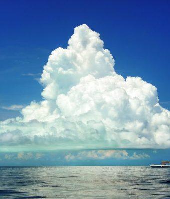 Paisaje con un gran cúmulo que se eleva hacia el cielo desde la costa, que se ve al fondo. A media distancia, un barco pequeño refuerza la majestuosidad y el tamaño enorme de la nube.