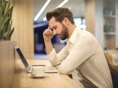 Hombre mirando a su ordenador pensativo.