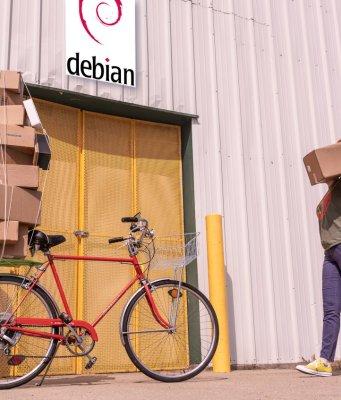 Entrada de una factoría que tiene un cartel de Debian sobre la puerta de entrada. Una mujer trae un paquete. Parece haber aparcado una bici con más paquetes, sujetos con un pulpo (elástico).