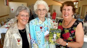 From left, Beeac Red Cross president Alma Black, Ailsa Sims and Dawn Missen with a copy of the book  The Wattle's Call and Other Stories which the group launched at Beeac Red Cross's 100-year anniversary.