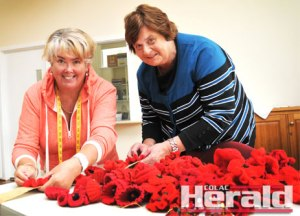 Heather Green, of Colac Quilters, and Mary Prime gather a field of knitted and crocheted poppies for an Anzac Day poppies display to commemorate Colac district soldiers who died in the First World War.