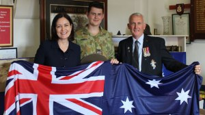 Winchelsea's Mitchell Woods, centre, and his father Stephen will travel to Turkey next month for the 100-year anniversary of the Gallipoli landings. Corangamite MP Sarah Henderson presented the duo with an Australian flag to take on the trip.