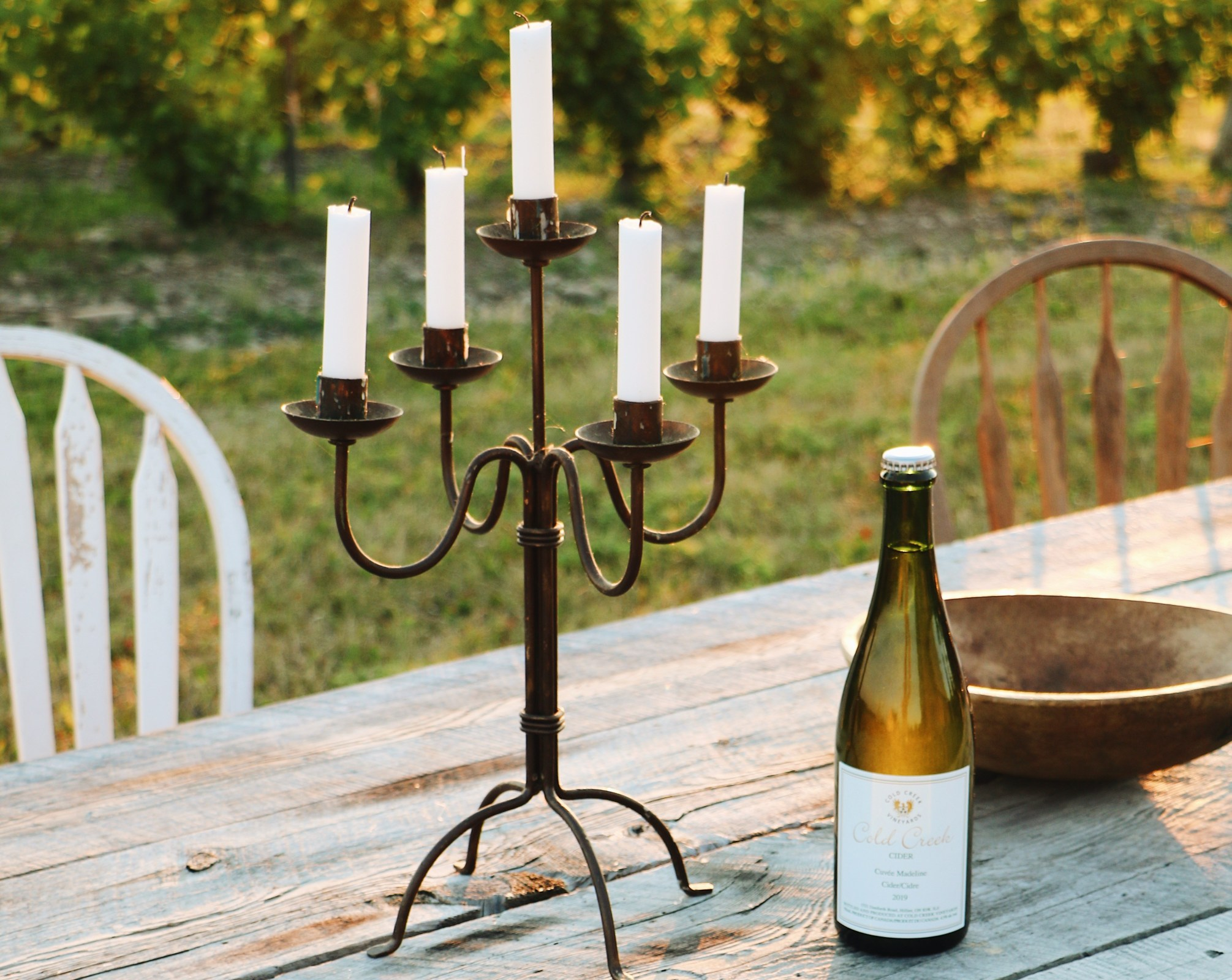 Bottle of cider sits on table beside antique candelabra with vineyard view in the background.