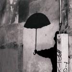 man with dark umbrella by Camil Tulcan