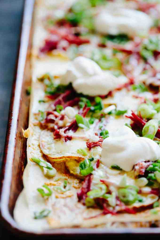 SHEET PAN IRISH NACHOS | Crispy roasted potatoes topped with melted Irish cheddar, shredded corned beef, scallions and sour cream. The perfect pub food to serve on St. Patrick's Day with a pint! #Irish #potatoes #nachos #cheesy #cheddar #corned #beef #sheetpan #easy #recipe | ColeyCooks.com