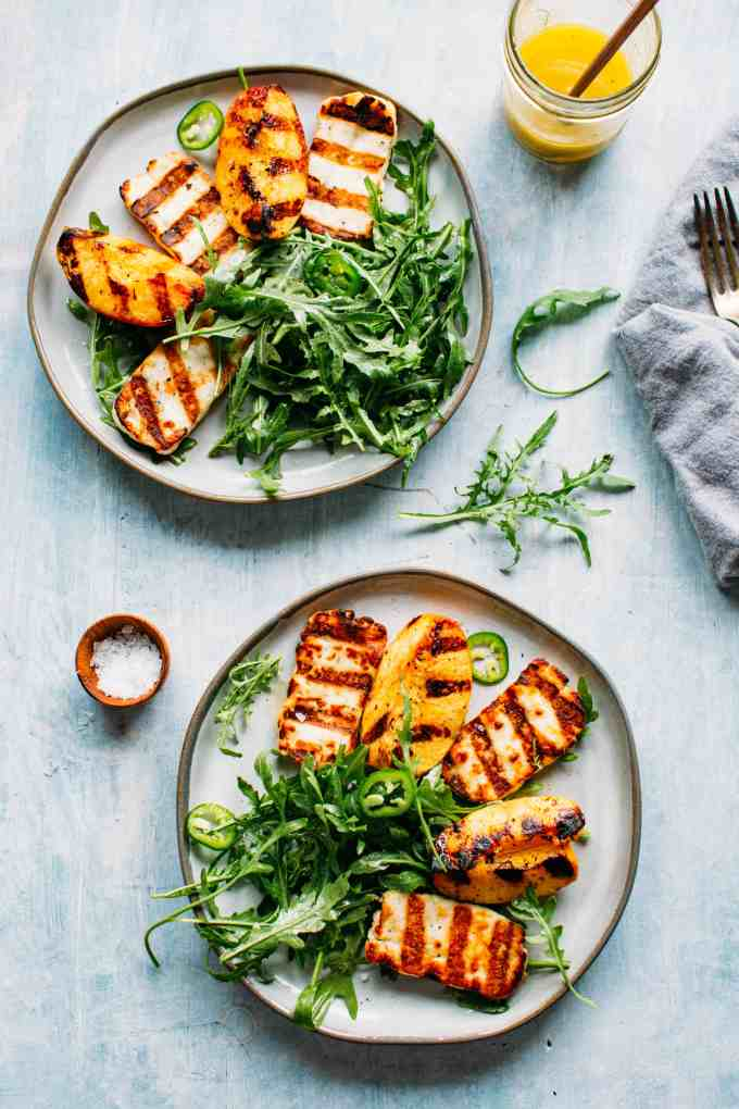Two plates of grilled halloumi and peaches with arugula, jalapeños and honey lemon vinaigrette