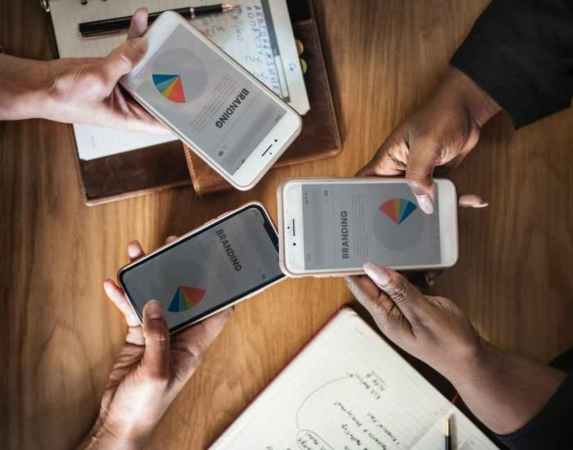 three people holding phone displaying branding pie chart
