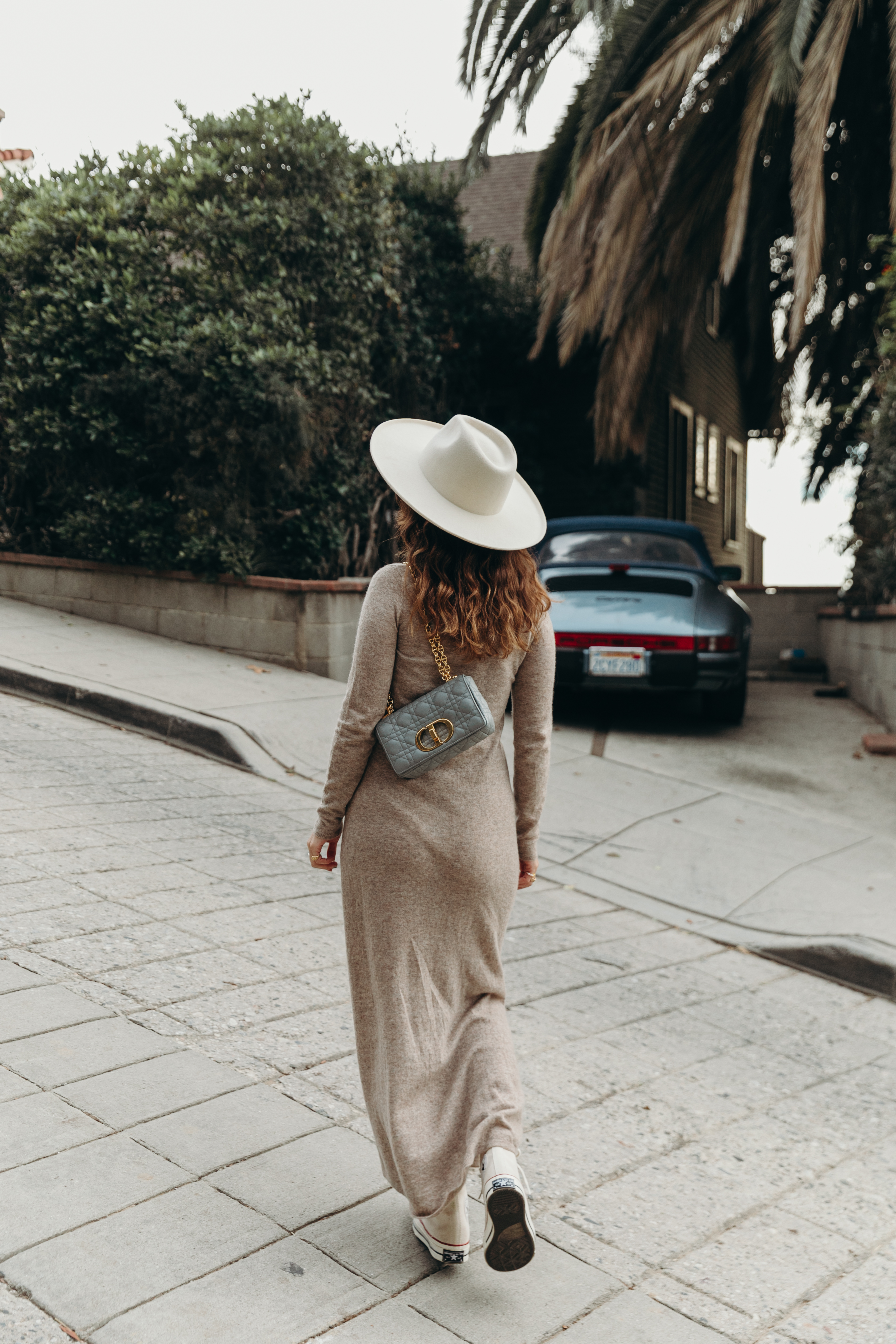 Sara from Collage Vintage wearing a midi knit dress, all star sneakers and cloud blue Caro Dior bag