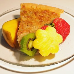 A piece of rich, custard Bean Pie, garnished with fresh mango, kiwi, pineapple and a strwberry makes for a great gluten free dessert.