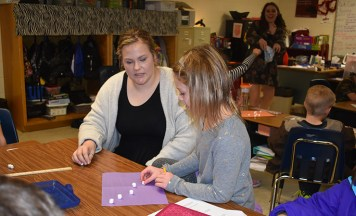 Courtney Cox helps a student design a constellation using marshmallows.