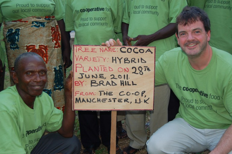 Brad planting his own cocoa tree in Ghana at Kuapa Kokoo