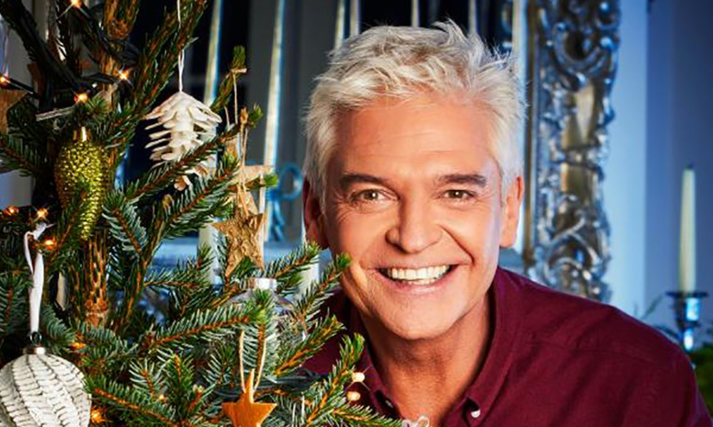 Philip Schofield by a Christmas tree