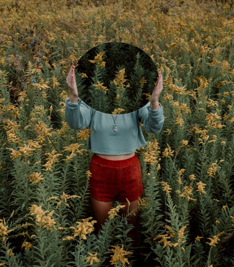 woman holding mirror in a field