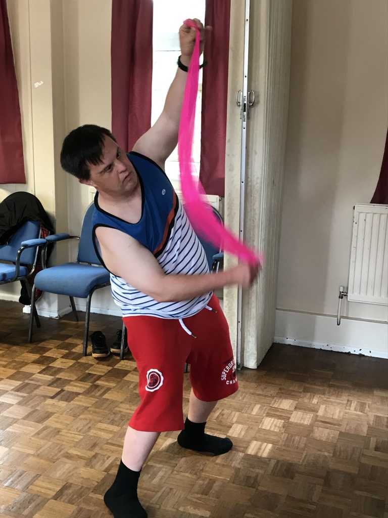 Adult with Downs Syndrome dancing with a scarf