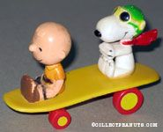 Charlie Brown & the Flying Ace sitting on yellow curved skateboard