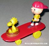 Woodstock sitting in nest and Charlie Brown standing on red curved skateboard