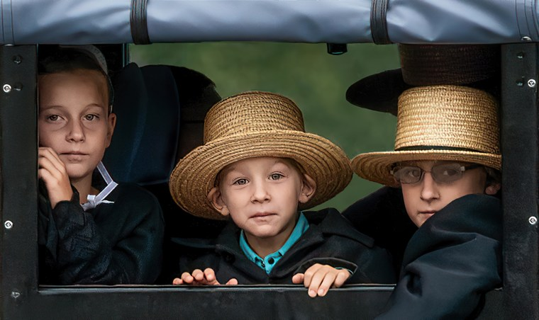 Three Amish children on their way to Sunday services looking out the back window of their buggy