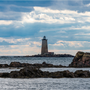 Maine lighthouse at low tide exposing rocky Maine shoreline