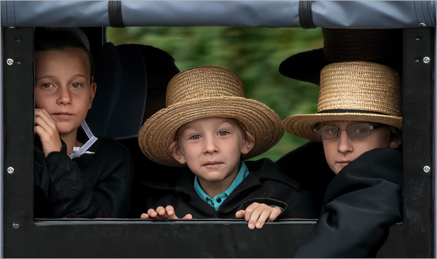 3 Amish children going to Sunday services look out of back window of buggy