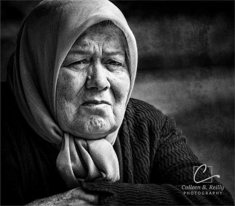 Older woman wearing scarf looking pensively into the distance