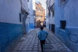 """A boy runs through the quiet streets of Chefchaouan the """"Blue City"""" in northern Morocco. October 2015."""