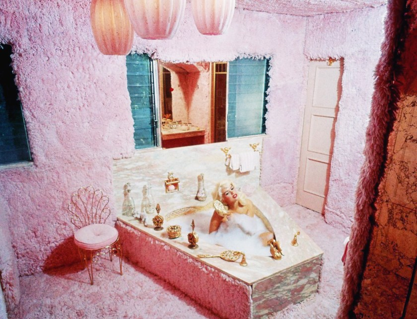 Jayne Mansfield's Pink Palace | Jayne brushes her blonde hair in her pink fur bathroom.