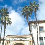 The old main gate of Paramount Studios with palm trees and blue sky in the background.