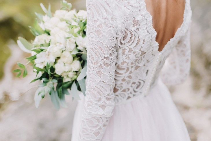 Bride in a white lace wedding dress holding a bouquet getting ready to walk down the aisle at her wedding