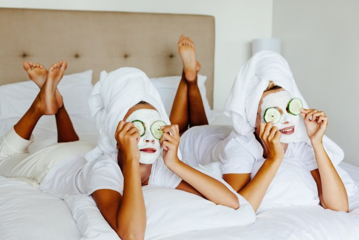 two women laying in bed with face masks on, towels on their head and cucumbers on their eyes