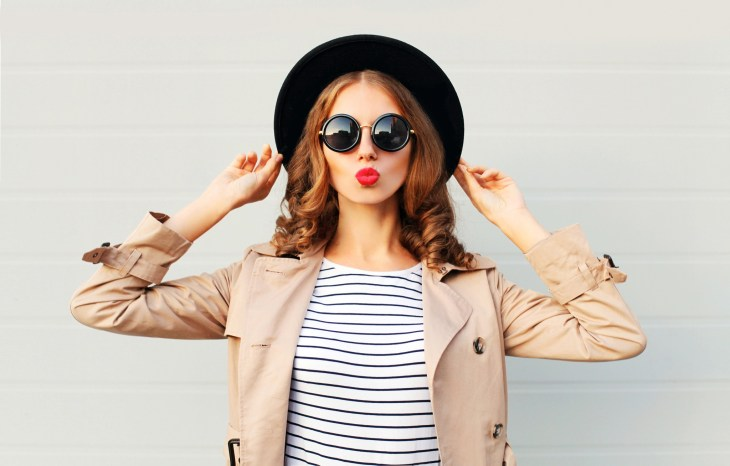 Women wearing red lips, fedora, striped shirt and blowing a kiss