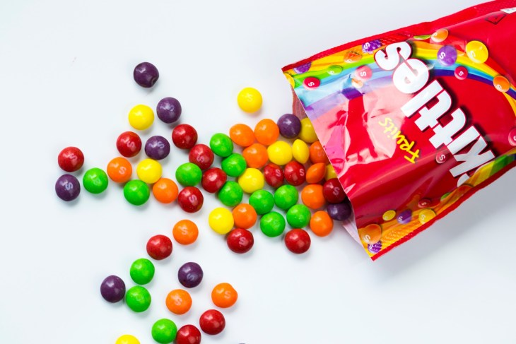 Skittles spilling out of the bag on to a white counter top