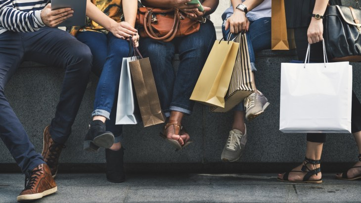Group of friends shopping and holding many shopping bags