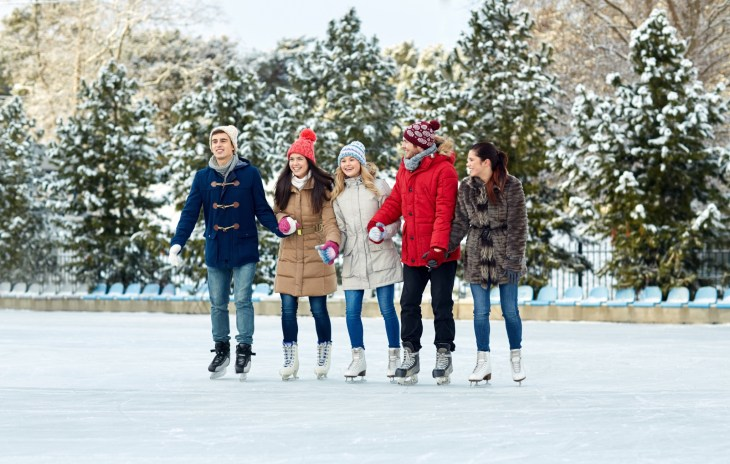 Group of friends ice skating outside during the winter