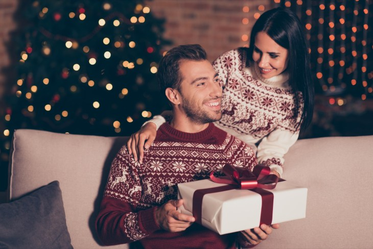 woman giving her man a gift on Christmas day