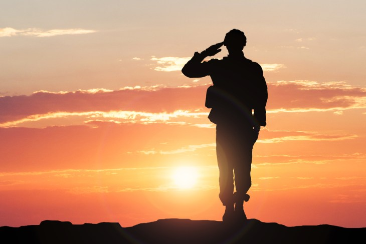 Soldier saluting in the sunset