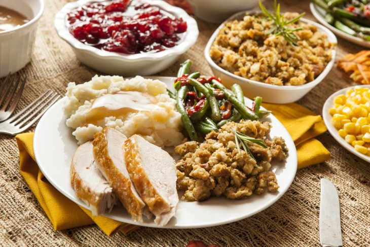 Thanksgiving dinner with turet, mashed potatoes, stuffing and green beans on a plate