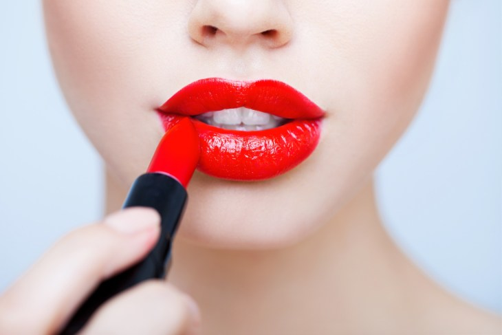 woman putting on bright red lipstick 2019 beauty trend