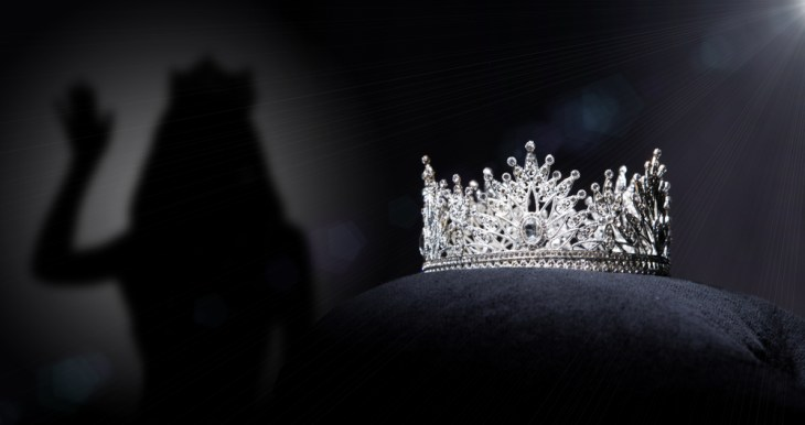 Jeweled crown sits on top of a black pillow with a pageant contestant shadow behind