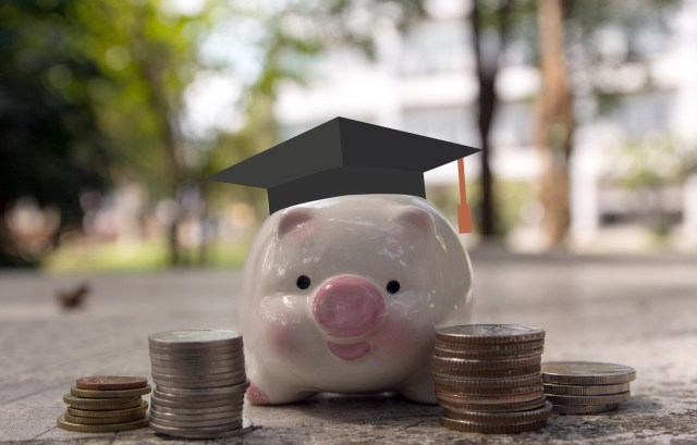 piggy bank with a graduation cap on with coins